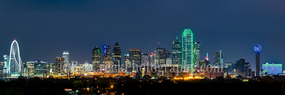 This is a photo of a Dallas skyline panorama at night which includes many of the iconic structures like the Margaret Hunt Hill bridge, Bank of America, Fountain Place, to the Reunion Tower with the alway changing and colorful Omni hotel