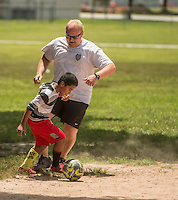 NWA Democrat-Gazette/ANTHONY REYES • @NWATONYR<br /> Colton Brind, 9, tries to get past Travis Beyer, with the Springdale police department, Wednesday June 24, 2015 during a soccer game at Jones Elementary School in Springdale. Beyet and other officers were there as part of the Sandlot Program where they help mentor the students through play. The officers open up the gymnasium to the children who play and can eat lunch at the school free of charge.