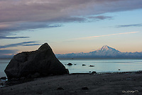 Mount Redount receives light from the rising sun during a cold morning on the beach at Kenai, Alaska.