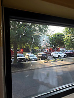 Emergency personnel are seen through a window with a bullet hole in Alexandria, Va., Wednesday, June 14, 2017. House Majority Whip Steve Scalise of Louisiana and others were shot Wednesday at a congressional baseball practice, officials said. (Joseph Miscavige via AP)