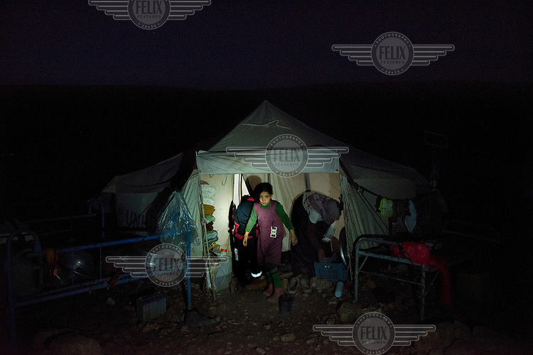 A Yazidi girl emerges from her tent in a Yazidi refugee camp in the Sinjar mountains in the early morning. <br /> Thousands of Yazidis fled to the mountains when Islamic State (IS) fighters attacked towns and villages around Sinjar in August 2014. Since then Yazidi refugees have been living in precarious conditions with no electricity or running water and children haven't been attending school. Support from the international community has been insufficient and people are dying of hunger and disease. Until December 2014 the mountains were surrounded by IS. Now the southern part of the mountains is still under IS control.