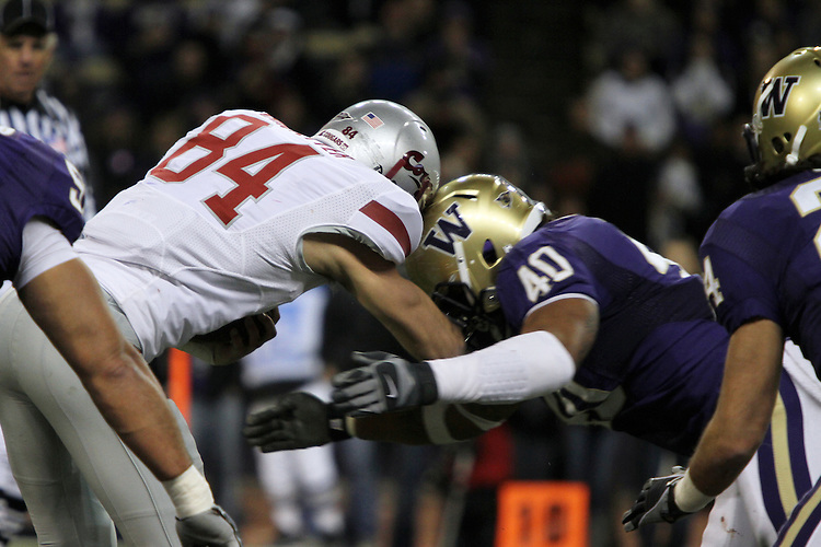 "Jared Karstetter (#84), Washington State sophomore wide receiver, absorbs a ""helmet-to-helmet"" shot from the Husky senior, Mason Foster (#40), during the Cougars Pac-10 conference ""Apple Cup"" showdown with arch-rival Washington at Husky Stadium in Seattle, Washington, on November 28, 2009.  The Cougars lost to the Huskies in the game, 30-0."