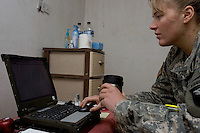 First Lieutenant Jennifer Wynn 24 years old from from Kennett Square Pennsylvania , Battalion maintenance officer of 1st Battalion, 506th, 101st airborne Division works on her laptop in her room at Combat Outpost (C.O.P)  in Eastern Ramadi, Al Anbar Province, Iraq on Wednesday JAN 11 2006. she has been in the military since MAY 2004. she has not yet decided  if she will  be a career officer in the US   ARMY.