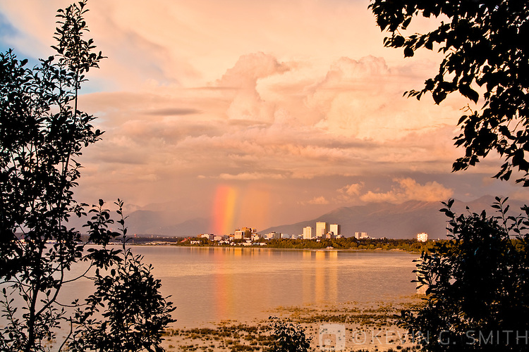 Anchorage skyline and rainbow at sunset, dramatic clouds, reflection in water, summer, shot from Earthquake Park