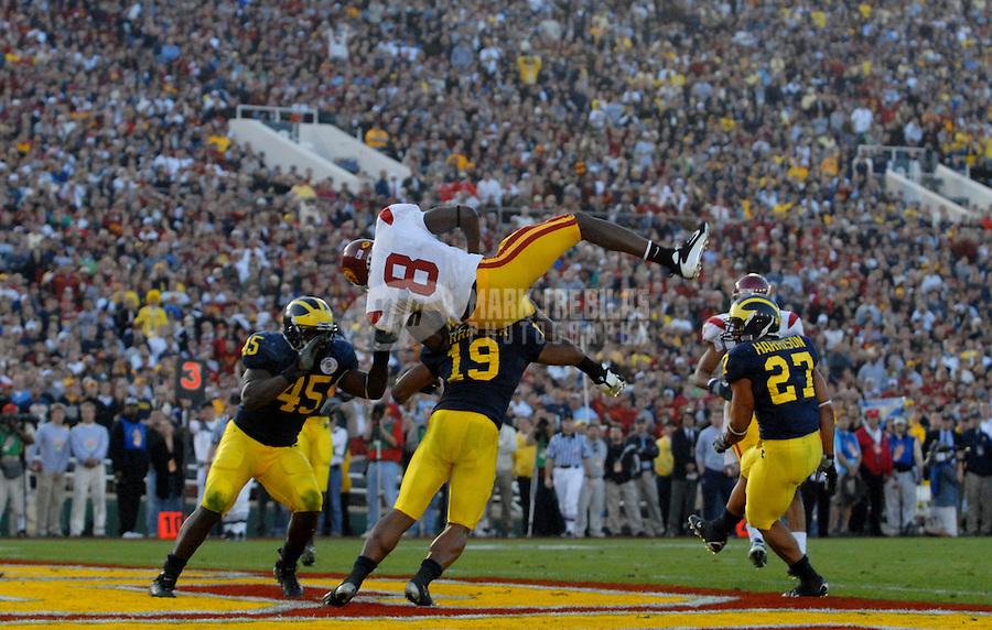 Jan 1, 2007; Pasadena, CA, USA; Southern California Trojans wide receiver (8) Dwayne Jarrett gets upended by a Michigan Wolverines defender in the Rose Bowl game at the Rose Bowl in Pasadena, California. Southern California defeated Michigan 32-18. Mandatory Credit: Mark J. Rebilas