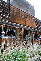 The broken windows and gapping door of this abanonded tavern stare blindly through overgrown weeds just off the lonely highway 225 north of Elko near the Nevada Idaho border.