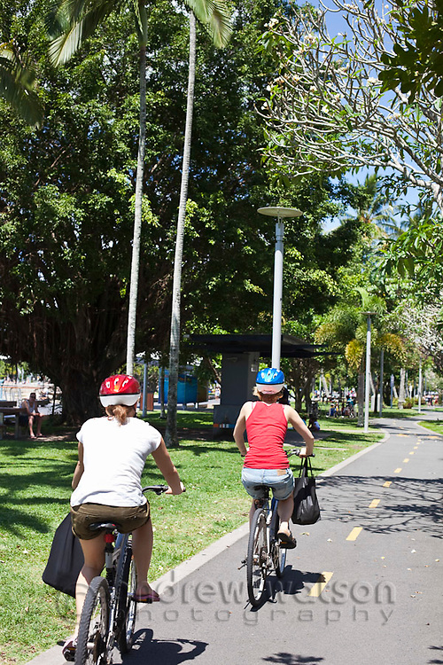 Tourists cycling along the Cairns Esplanade.  Cairns, Queensland, Australia