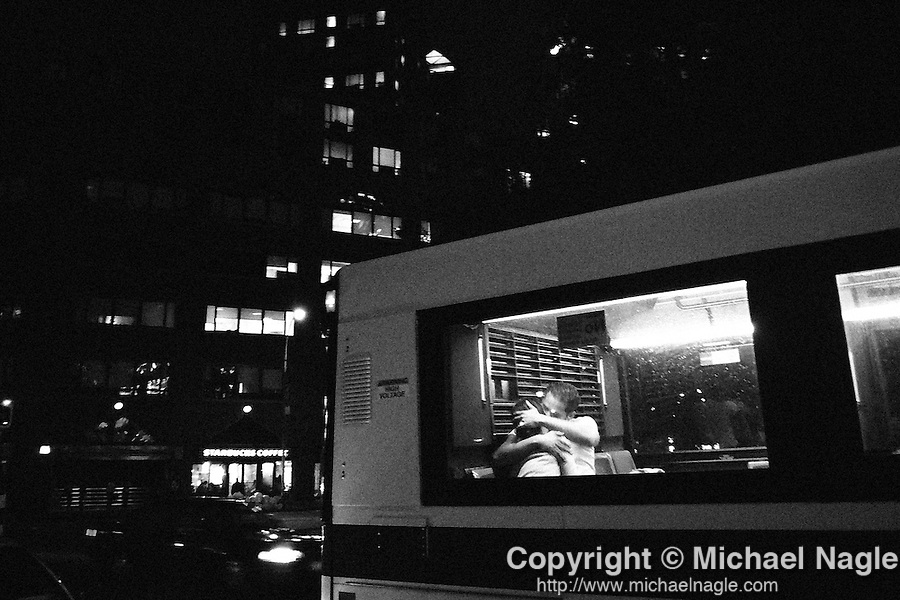 NEW YORK-- MAY 31:  A young couple kisses on the back of a bus heading south on Union Square East on May 31, 2006, in New York City.  (PHOTOGRAPH BY MICHAEL NAGLE)