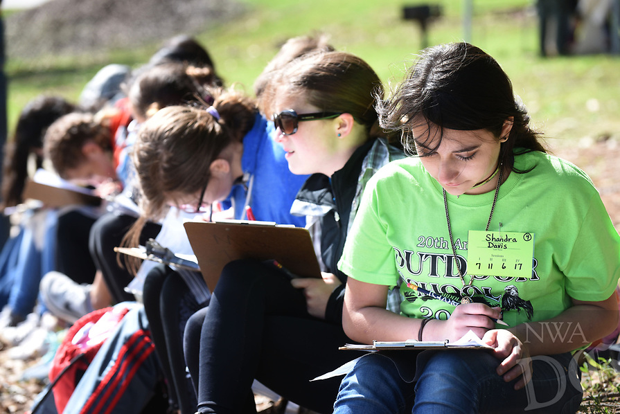 NWA Democrat-Gazette/FLIP PUTTHOFF <br /> Shandra Davis (right) and Makayla Wolfe (second from right) work on their outdoor stories at the 20th annual Lingle Middle School Outdoors School at Prairie Creek park.