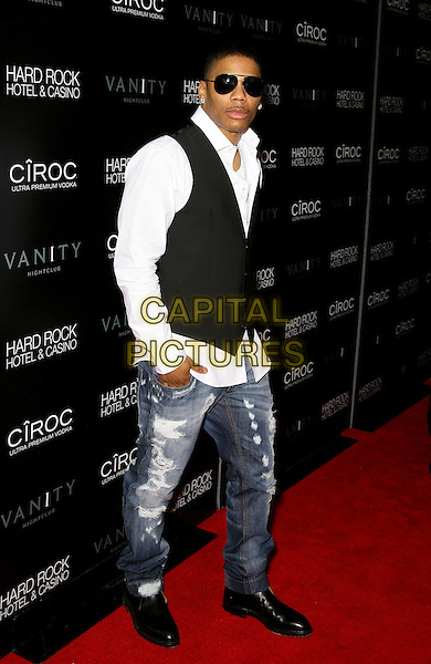 NELLY (Cornell Haynes, Jr.).grand opening of Vanity Nightclub at Hard Rock Hotel and Casino, Las Vegas, Nevada, USA, .2nd January 2010..full length jeans white shirt sunglasses waistcoat black shoes destroyed denim distressed .CAP/ADM/MJT.©MJT/Admedia/Capital Pictures