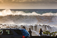 Spectators watching giant waves crashing against rocks during an large winter swell at Shark's Cove, North Shore, Oahu