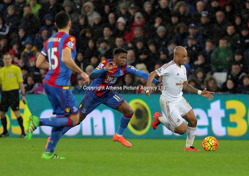 Andre Ayew of Swansea (R) is held back by Wilfried Zaha of Crystal Palace (C) during the Barclays Premier League match between Swansea City and Crystal Palace at the Liberty Stadium, Swansea on February 06 2016