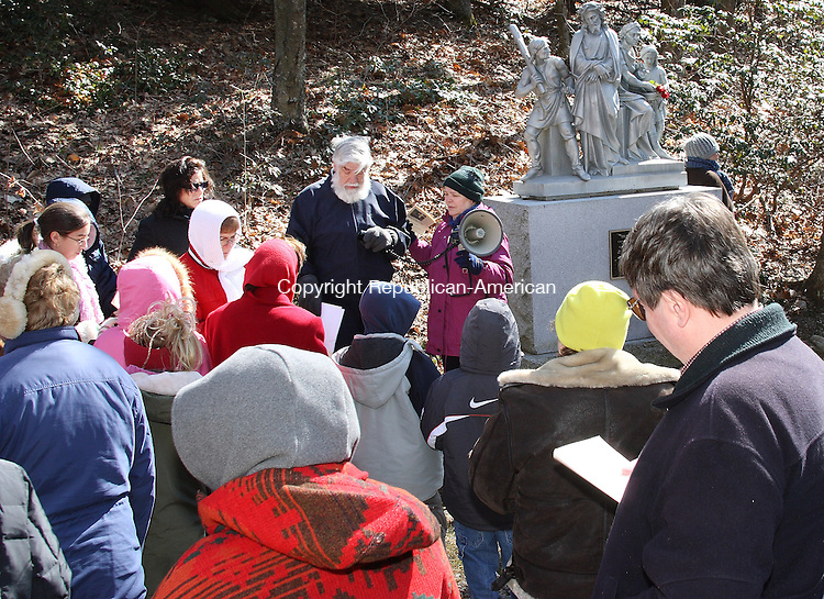 (center) Gerry and Susan White lead dozens of Good Friday observers who gathered to celebrate the Way of the Cross service at Shrine of Lourdes in Litchfield Friday morning. Stations depicting the crucifixion and resurrection of Jesus are positioned along a paved path in the woods on the Shrine's grounds. . Michael Kabelka / Republican-American