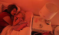 Heather Jacobs lays in the dark with her daughter, Ella, 3, at bedtime in their Polk City home.  Bedtime is cherished by Heather, as it is about the only time in the day where she will get one-on-one time with each of her children. Heather lost her husband, Eric, in a plane crash in 2006 when she was eight months pregnant with their youngest, Ella, and has since been raising her five young children on her own.