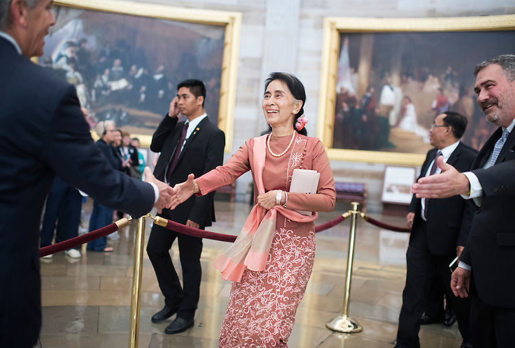 UNITED STATES - SEPTEMBER 15: San Suu Kyi, State Counsellor of Myanmar, greets Frank Larkin, left, Senate Sergeant At Arms, in the Capitol Rotunda between meetings with House Minority Leader Nancy Pelosi, D-Calif., and Senate leaders, September 15, 2016. Ted Daniel, of the House Sergeant At Arms, appears at right. (Photo By Tom Williams/CQ Roll Call)