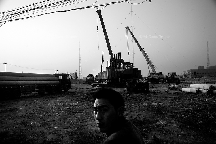 A man looks out onto a previously demolished area that will be developed into high-rise apartment buildings in Nanjing, Jiangsu, China.  Though the old buildings aren't yet fully demolished, cranes have already moved in to begin the new construction.
