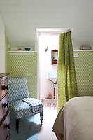 The traditionally styled guest bedroom has green pattern wallpaper and bathroom facilities in a recessed area.