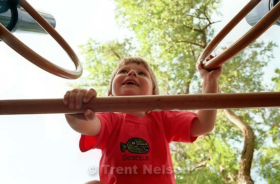 Noah Nelson climbing at playground.<br />
