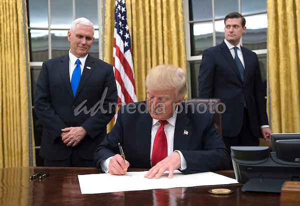 President Donald Trump signs a confirmation for Defense Secretary James Mattis in the Oval Office, at the White House in Washington, D.C. on January 20, 2017. Photo Credit: Kevin Dietsch/CNP/AdMedia