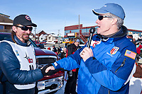 Lance Mackey is congratulated on his 4th consecutive Iditarod win by Exxon Alaska President of operations Dale Pittman at the finish line in Nome