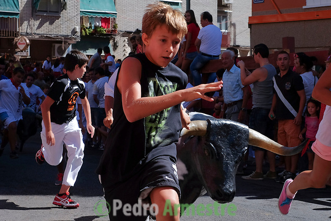 Children run ahead of a model bull used to train bullfighters after the first bull run of the San Sebastian de los Reyes Festival near Madrid, on August 26, 2014. © Pedro ARMESTRE