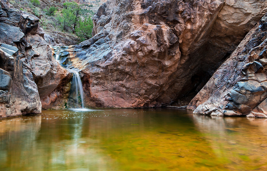 """A small stream of water falls into a pool along the trail going up into No Thoroughfare Canyon in Colorado National Monument.  The trail extends from the """"Devils Kitchen"""" found at the first part of the trail."""