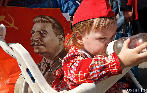A baby drinks milk during a Communist march in central Moscow on Victory Day with portraits of Soviet dictator Josef Stalin.