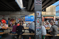 People drinking beer in an outside bar underneath the U-Bahn bridge in Alexanderplatz, Berlin, Germany. Picture by Manuel Cohen