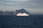 Cruise ship passing mountains of Lofoten Islands, Nordland, Norway