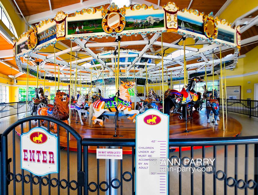 Nunley's Carousel, full wide angle view from inside Pavilion, with sign showing how tall riders must be to ride alone, at Museum Row, Garden City, New York, USA, on August 7, 2012