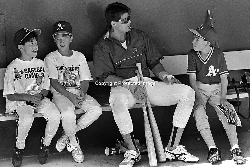 Oakland Athletics outfielder Jose Canseco with group of little leaguers,( 1972 photo by Ron Riesterer)