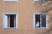 The facade of a building typical for the 1940s 1950 is Sweden in typical coloured fresco material with two square windows and a woman sitting in one open window with her back to the camera smoking a cigarette Stockholm, Sweden, Sverige, Europe