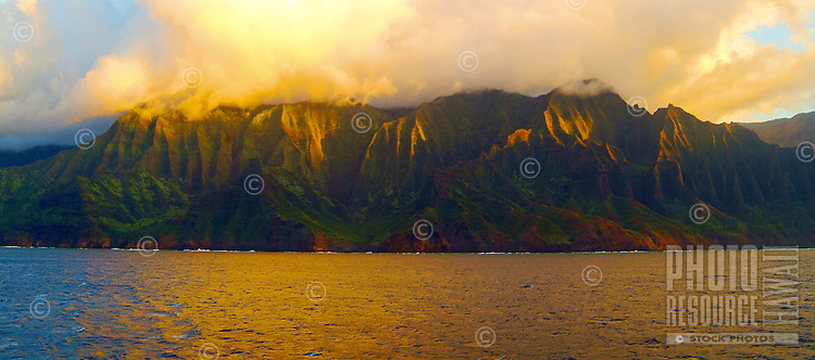 Golden sunset light skims across the rugged cliffs of Na Pali, Kauai, along the eleven mile Kalalau Trail.