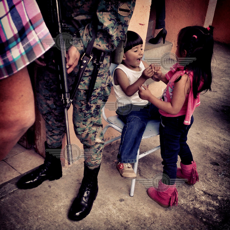 Children play outside a polling station where an armed military guard is keeping watch during voting in local elections.