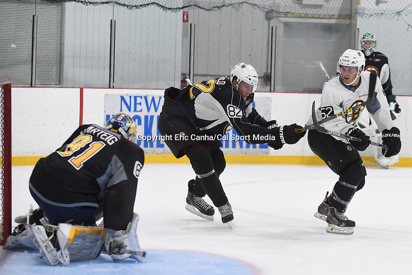 July 15, 2015 - Wilmington, Massachusetts, U.S. - Defenseman Brandon Carlo (82) and forward Alex Iafallo (62) work on a drill in front of goalie Michael Garteig (81) at the Boston Bruins development camp held at Ristuccia Arena in Wilmington Massachusetts. Eric Canha/CSM