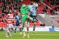Matthew Bloomfield of Wycombe Wanderers (right) challenges Ross Etheridge of Doncaster Rovers for the ball before scoring the opening goal during the Sky Bet League 2 match between Doncaster Rovers and Wycombe Wanderers at the Keepmoat Stadium, Doncaster, England on 29 October 2016. Photo by David Horn.