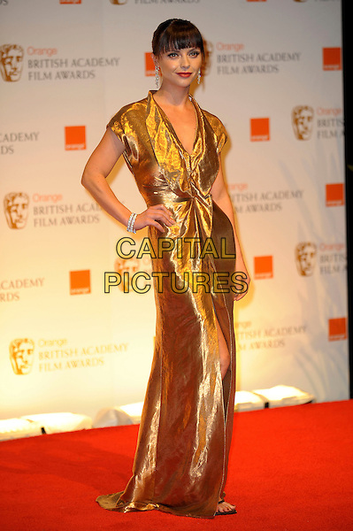 Christina Ricci.Pressroom at the Orange British Academy Film Awards 2012 at The Royal Opera House, London, England..February 12th, 2012.press room bafta baftas full length gold dress hand on hip.CAP/CAS.©Bob Cass/Capital Pictures.