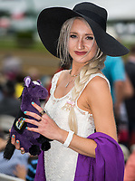 BALTIMORE, MD - MAY 20: A woman holds a purple stuffed animal horse with a Preakness saddlecloth as she poses for a photo in the grandstand on Preakness Stakes Day at Pimlico Race Course on May 20, 2017 in Baltimore, Maryland.(Photo by Douglas DeFelice/Eclipse Sportswire/Getty Images)
