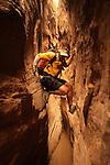 A young man navigates a slot canyon while canyoneering in southern Utah.