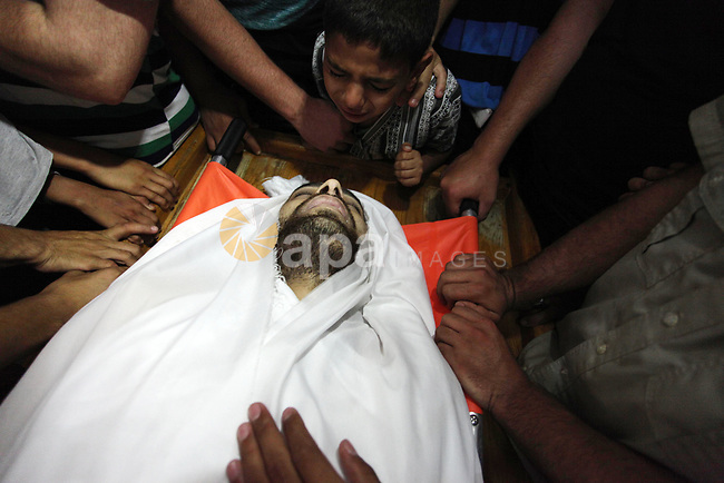 Palestinian relatives mourn over the body of Yussef al-Faseeh, 29, who was shot dead by Israeli troops during clashes at Israel-Gaza border, during his funeral in Gaza city on on 9, 2018. Four Palestinians were killed by Israeli fire on the Gaza border on June 8, the territory's health ministry said giving a new toll, as weeks of deadly clashes with protesters continued. Photo by Mahmoud Ajour