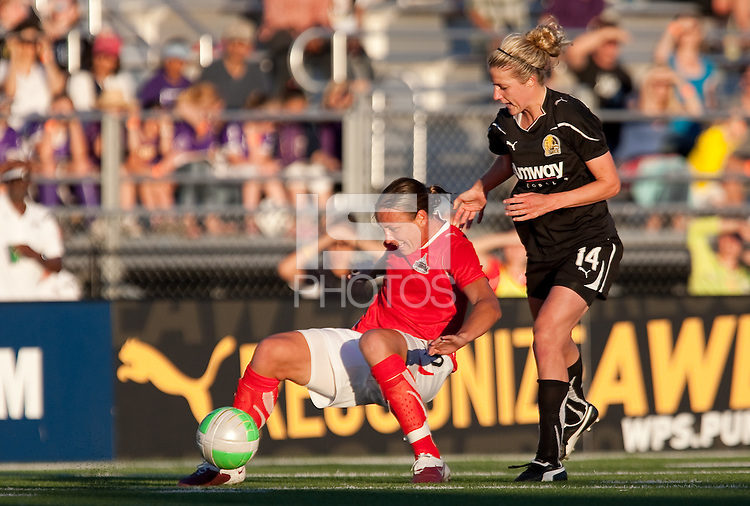Abby Wambach (left) controls the ball underneath Becky Edwards (14). FC Gold Pride tied the Washington Freedom 1-1 at Castro Valley HS Athletic Stadium in Castro Valley, California on June 5th, 2010.