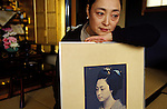 Kyoto, Japan..Mineko Iwasaki posing at home with a photograph from the days when she was Kyoto's most famous geisha...All photographs ©2003 Stuart Isett.All rights reserved.