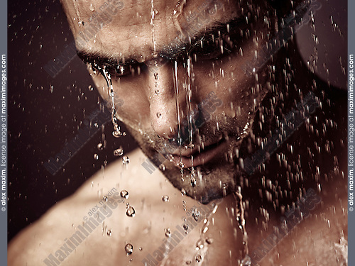 Pensive troubled man face under pouring shower dramatic emotional portrait.