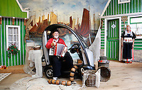 Nederland Volendam 2015 06 28. Man in Volendamse klederdracht in een scootmobiel, laat zich fotograferen bij fotograaf Zwarthoed