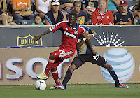 CHESTER, PA - AUGUST 12, 2012:  Keon Daniel (26) of the Philadelphia Union holds on to  Patrick Nyarko (14) of the Chicago Fire during an MLS match at PPL Park, in Chester, PA on August 12. Fire won 3-1.