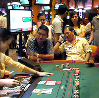 Gamblers play on Baccarat tables in a casino, in Singapore, on March 13, 2010. Photo by Juha-Pekka Kervinen/Pictobank