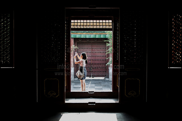 A Chinese girl takes a picture in the Summer Palace in Beijing, China, July 20, 2014.<br /> <br /> Smartphones are an essential tool of Chinese ordinary life. Everywhere in China, people use them to take pictures to share online, to talk and chat, to play videogames, to get access to the mainstream information, to get connected one each other. In the country where the main global social media are forbidden - Facebook, Twitter and Youtube are not available  -, local social networks such as WeChat have a wide spread all over the citizens. The effect is an ordinary and apparently compulsive way to get easy access to digital technology and modern way of communication. <br /> A life through the display. Yes, We Chat.<br /> <br /> © Giorgio Perottino