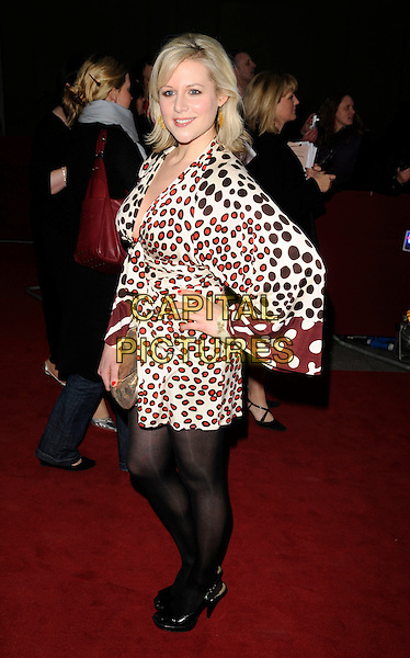 ABI TITMUSS.The Galaxy British Book Awards held at the Grosvenor Hotel, Park Lane, London, England. .April 9th, 2008 .full length black red cream white spotted print dress cleavage black tights gold clutch bag bracelets hand on hip.CAP/CAN.©Can Nguyen/Capital Pictures.