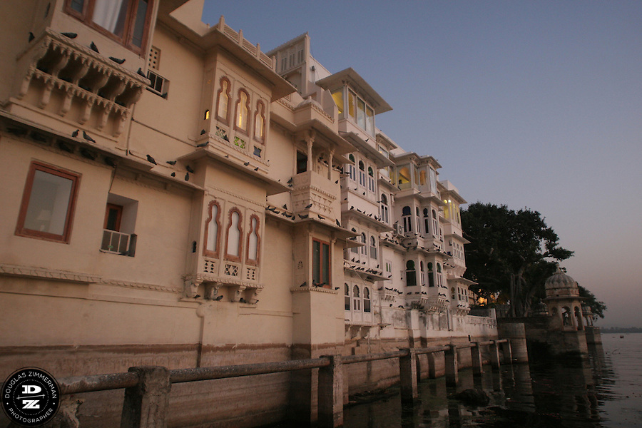 "Buildings along the waterfront of Pichola Lake in Udaipur, Rajasthan, India at sunset.  Udaipur is located in a valley surrounded by the Aravalli hills, and at its center is the Pichola Lake.  The scenic city has been described as ""the most romantic spot on the continent of India"" (by Colonel James Tod).  Photograph by Douglas ZImmerman"