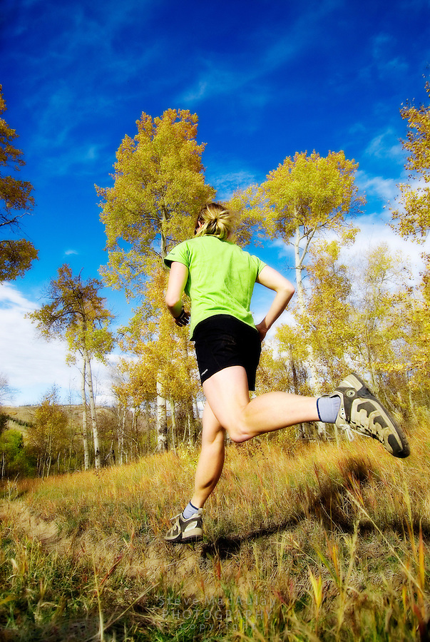 Young woman in black shorts and bright green singlet caught in mid stride on a Fall day trail run, Grand Teton National Park, Wyoming